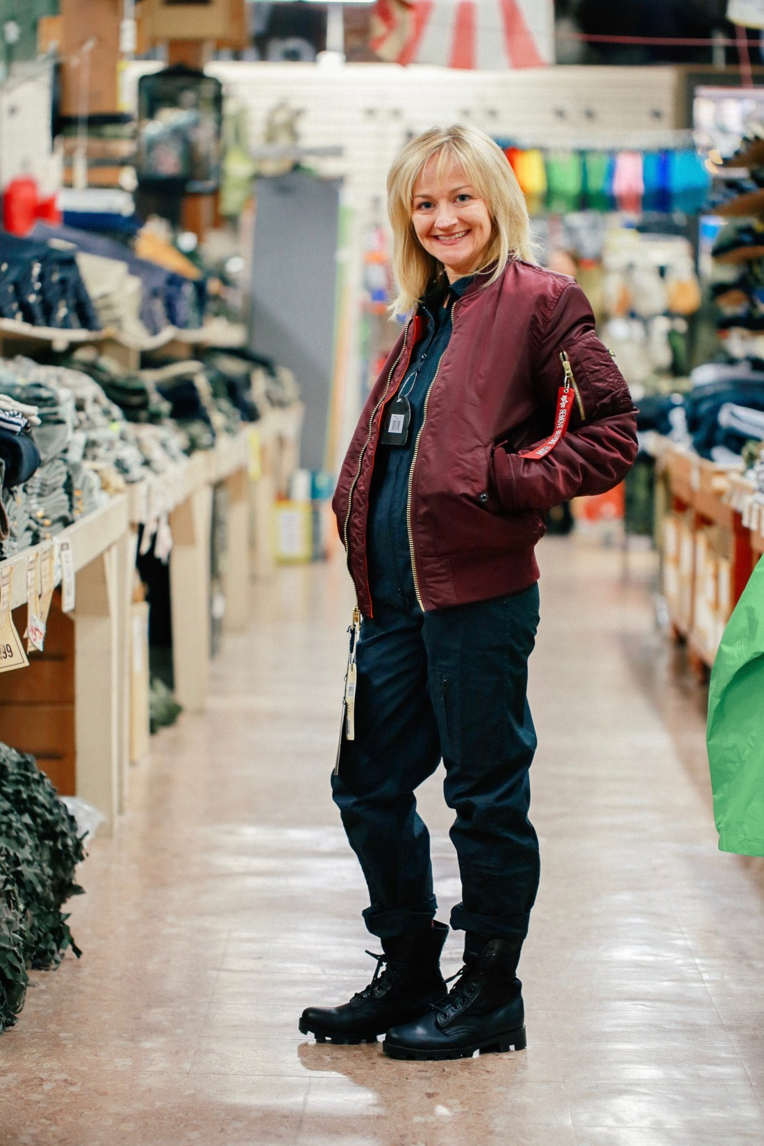 Black jumpsuit with burgundy satin bomber and black army boots available at Federal Army Navy Surplus in Seattle.