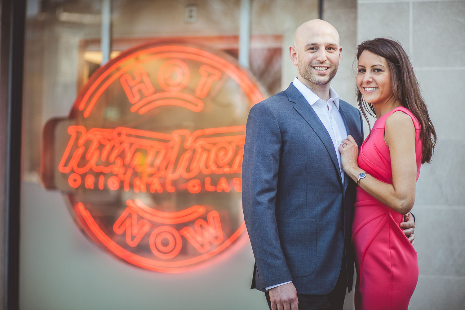Engaged couple in front of Krispy Kreme sign at Dupont Circle in DC.