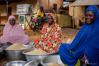 """Pudiques mais souriantes, trois vendeuses de riz """"local"""" espèrent un client à servir... En arrière plan, un conducteur de zémidjan (moto-taxi) profite d'une courte pause avant de reprendre du service. Les """"zem"""" comblent les lacunes en transports publics et permettent aux Béninois - indépendamment de l'état des routes et de l'heure du jour ou de la nuit - de se rendre dans n'importe quel coin de la ville, pour quelques centaines de francs CFA. // Kérou - 2019"""