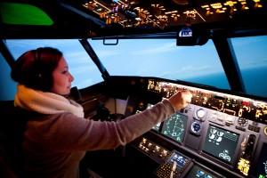 Une stagiaire utilise le système de pilotage automatique du simulateur de Boeing 737 de Paris. Observez aussi les nombreux écrans qui permettent de simplifier le cockpit.