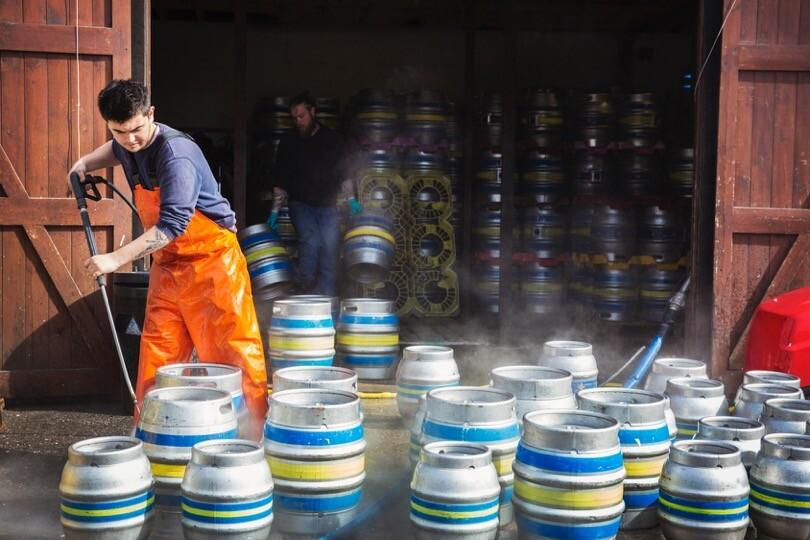 hombre desinfectando bidones cerveza -
