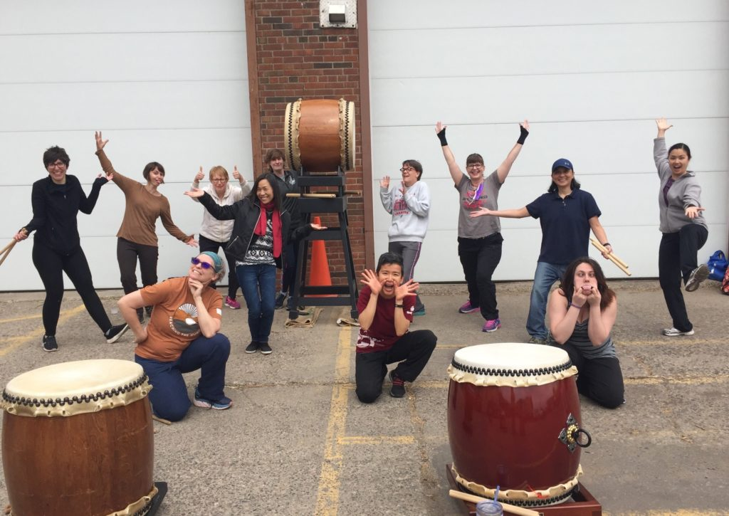 12 people including Marilou posing around some large drums.