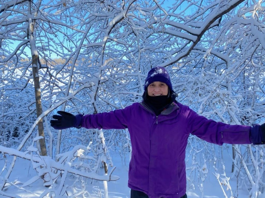 A picture of Marilou in front of several trees that have a lot of fresh snow on them.