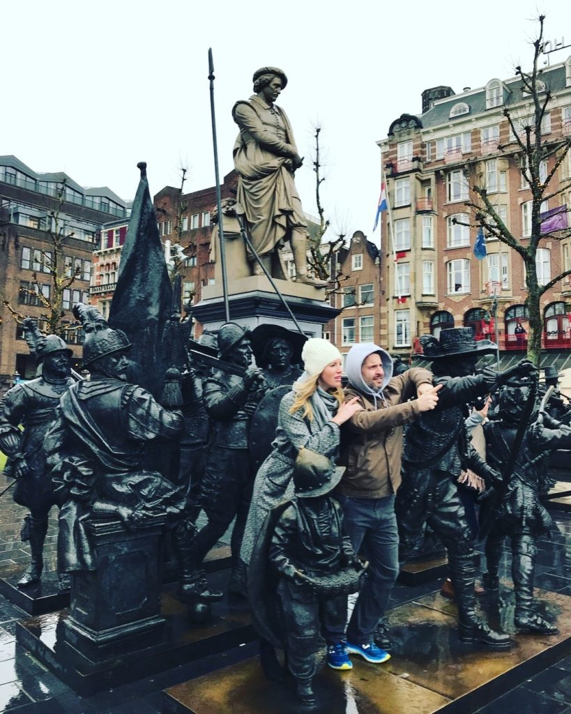 A picture of Kate and her husband in Amsterdam with some statues.