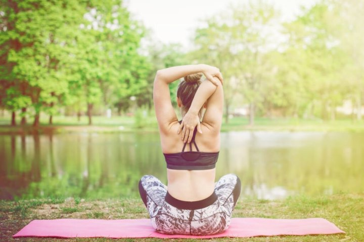 Young woman stretching arms before exercise