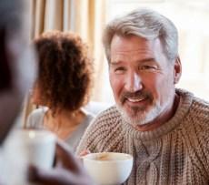 Smiling man holding coffee mug
