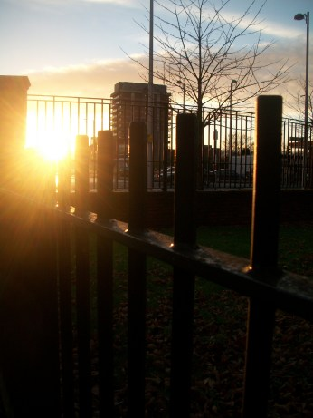 Sun setting low in the sky behind iron railings. Ardwick Green Manchester