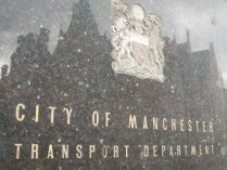 Sign on exterior of building, Ardwick, Manchester, with reflection.