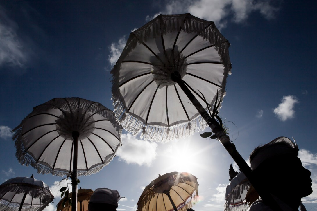 Procession of Umbrellas during a ceremony at Tanah Lot temple near the village of Tabanan, Bali, Indonesia.