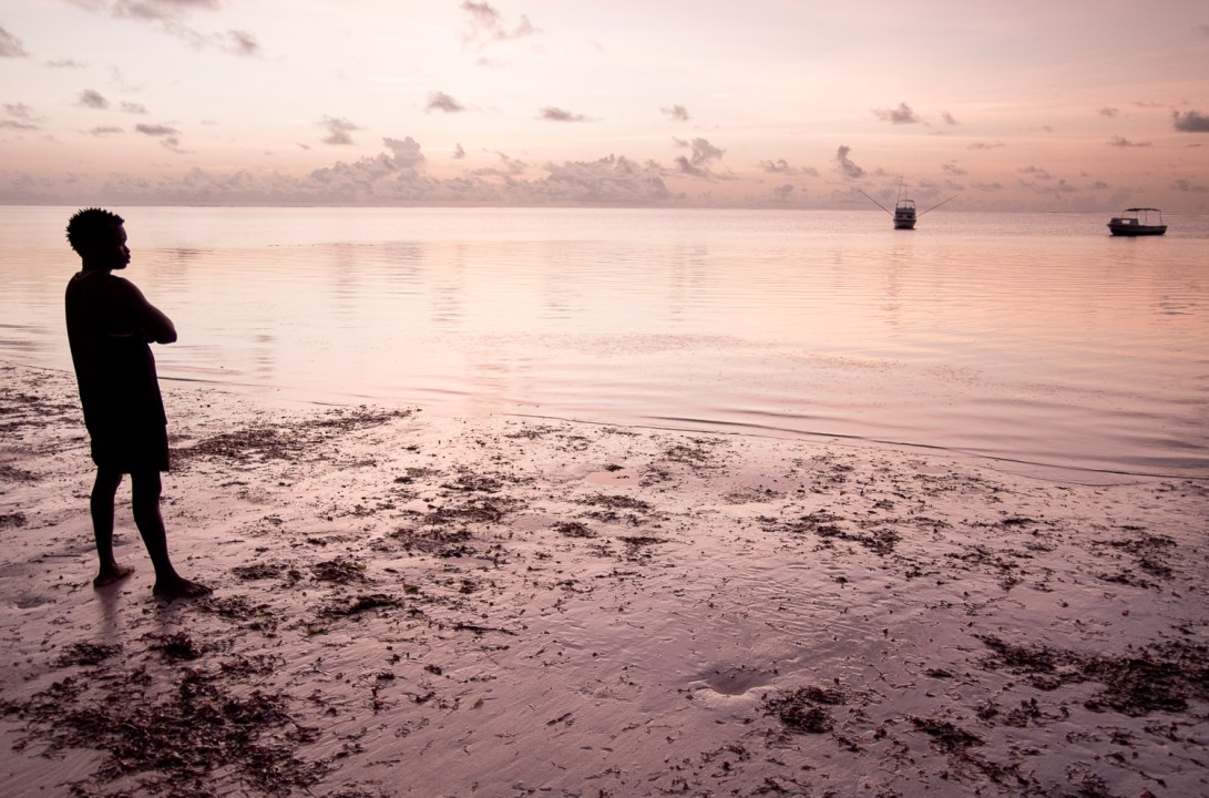 Bamburi beach, Mombasa at dawn as a man waits to begin the day and set up his boat.