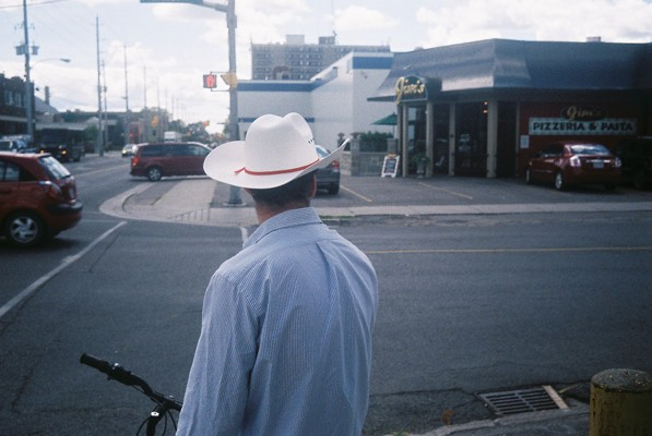 Man wearing a cowboy hat waits to cross the road in Peterborough, Ontario, Canada. Point and Shot analogue street photography.