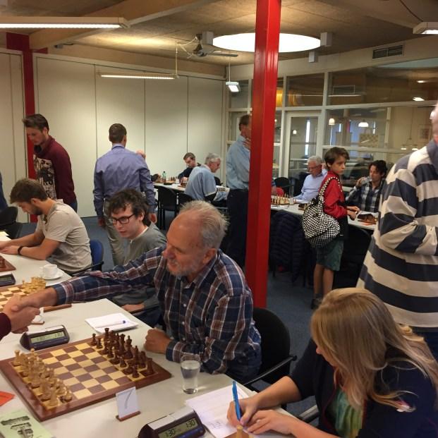 Herman van Halderen geeft zijn tegenstander een hand aan het begin van een schaakwedstrijd.