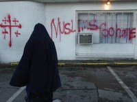 "Image of a Muslim woman facing graffiti on her home, which reads ""Muslims Go Home,"" alongside painted crucifixes."