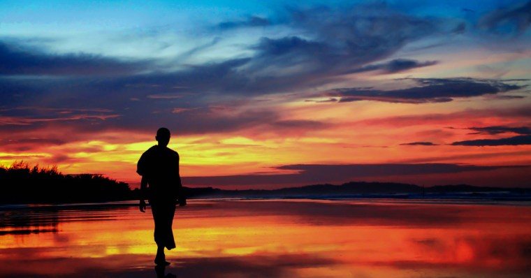 A photo of a man walking peacefully on the beech at sundown.