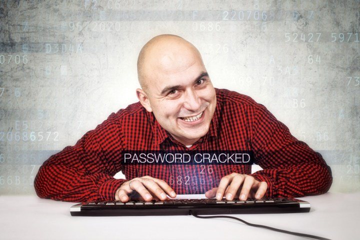 Computer hacker cracked security password. Bald smiling computer hacker typing computer keyboard.