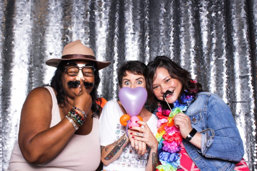 Three friends smiling and wearing props in the Culver City Photo Booth