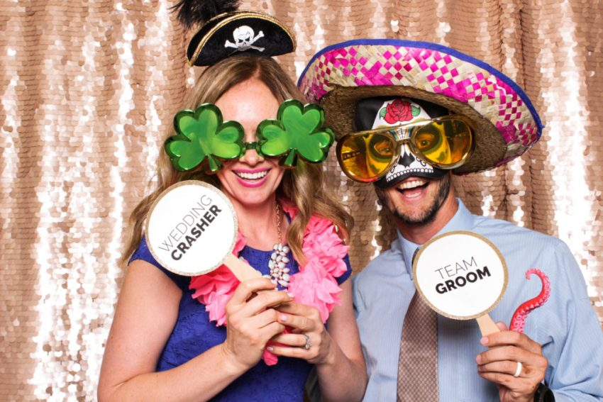 A girl and guy wearing hats, big glasses and holding signs in the Rancho Palos Verde Photo Booth