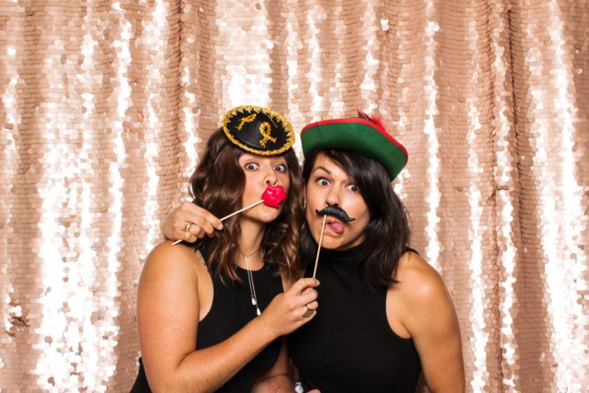 Two female friends wearing hats, and fake lips and mustaches in the Rancho Palos Verde Photo Booth