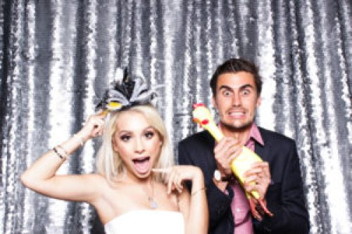 A couple wearing props and pulling cute faces in the photo booth