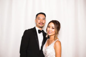 A happy bride and groom posing in the photo booth