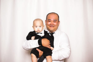 A father holding his small infant son in a tux in the photo booth