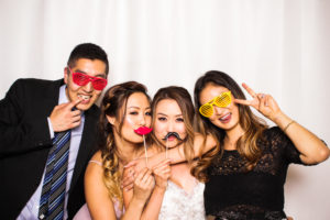 A bride posing with friends wearing props in the photo booth