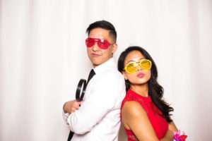 A couple standing back to back wearing colorful shades in the photo booth