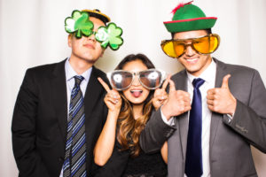 A girl giving the thumbs up next to two tall guys in the photo booth