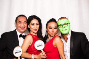 Two couples posing in the photo booth