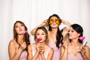 A bride and her bridesmaids posing with props in the photo booth
