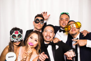 A bride and groom pulling funny poses with friends while wearing props in the photo booth