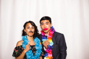 A couple wearing colorful garlands in the photo booth