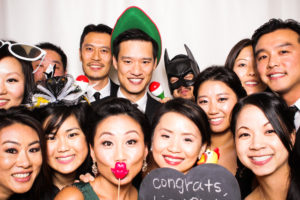 A big group of friends posing in the photo booth with a congratulations sign