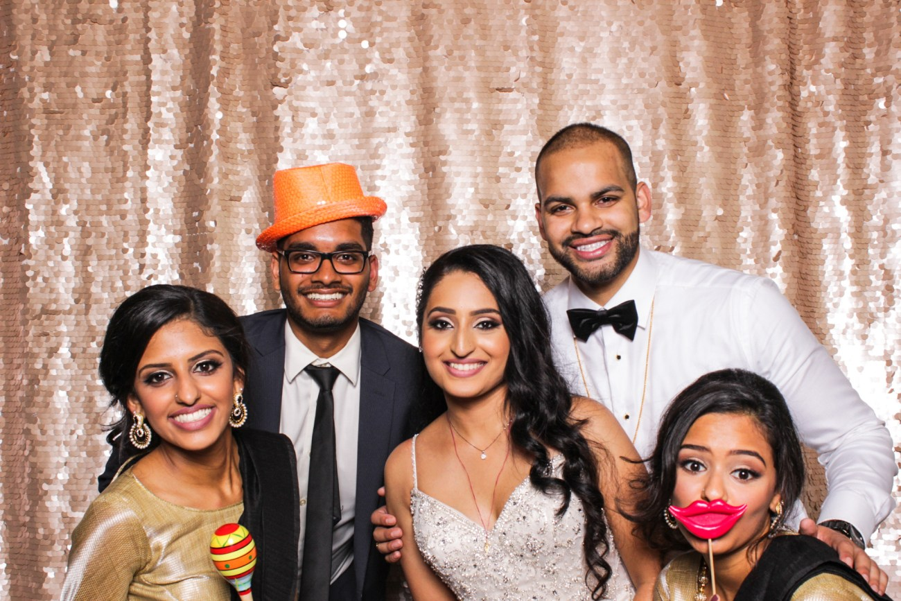 A bride and groom posing with some guests in the pasadena photo booth