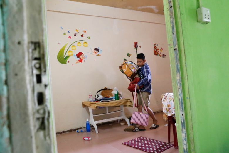 A boy prepares to move out of his apartment in Phnom Penh's White Building yesterday.