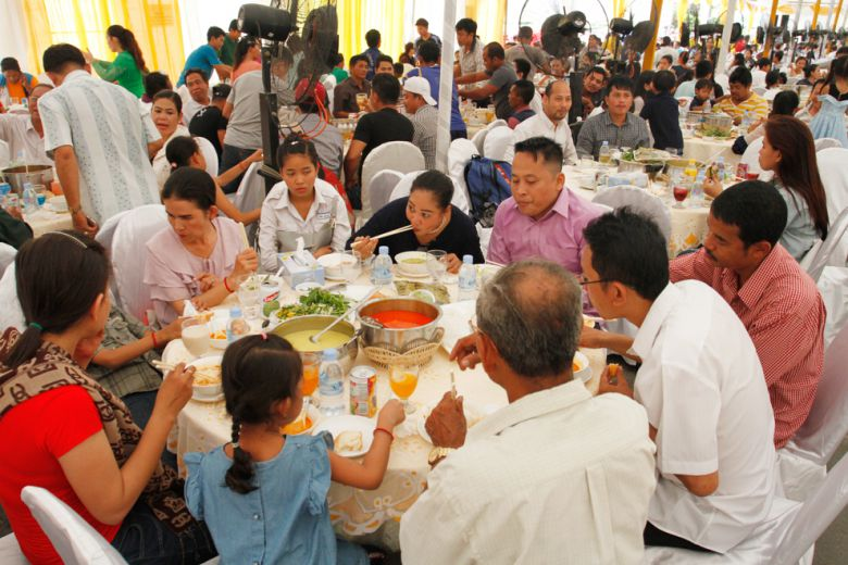 White building residents feast on the farewell noodle party thrown by the Ministry of Land Management on Saturday in Phnom Penh.