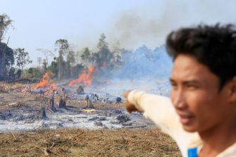 A former employee of Think Biotech, Khai Vanda, points at a large fire earlier this month in Kratie's Kampong Cham commune where the company has employed slash and burn techniques to clear land.