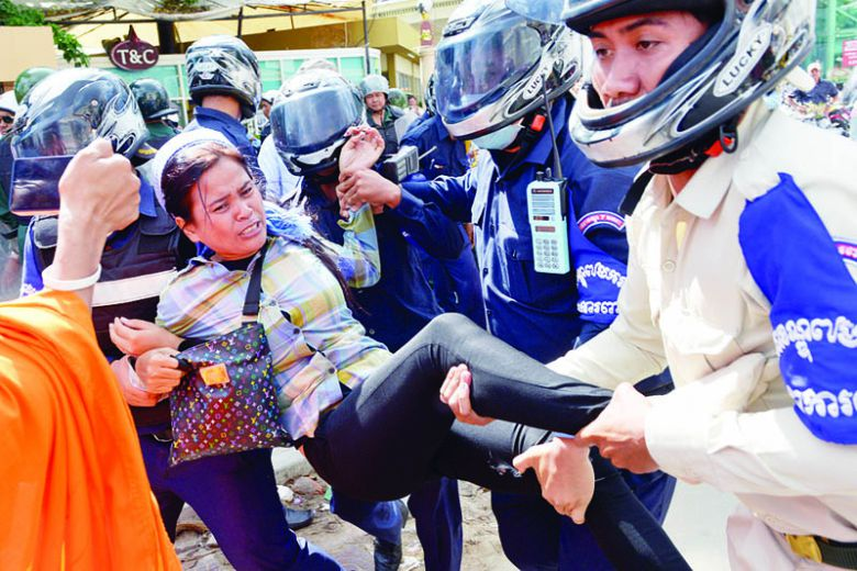 Security guards arrest a land rights activist from Boeung Kak lakeside community during a protest in front of Phnom Penh municipal court in 2014.