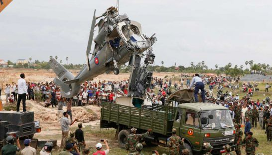 The wreckage of a Z-9 military helicopter is loaded on to a truck after it crashed during a training exercise on the outskirts of Phnom Penh