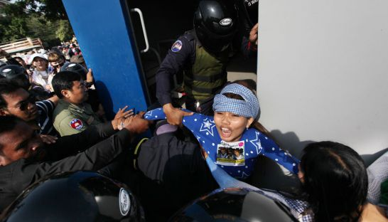 Land rights activist Yorm Bopha shouts as she is pulled into a police vehicle by authorities near the US embassy in Phnom Penh
