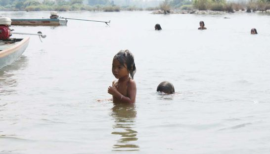 Local residents swim in the reservoir where the controversial Lower Sesan II Dam is planned in Stung Treng province