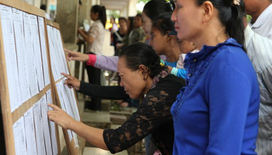 People look for their names on a voter list for the national election held in 2013 in Phnom Penh.