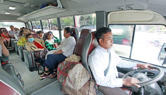 Passengers use the public bus service as a driver navigates Phnom Penh's Monivong Boulevard last year.