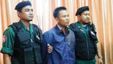 Police stand next to Oeut Ang last year at the Phnom Penh police headquarters after he was arrested for the murder of Kem Ley. Photo supplied