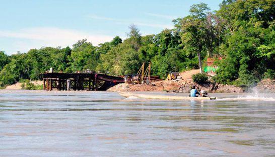 A man pilots a boat along a river