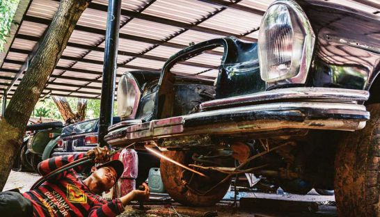A member of Ing Samath's restoration team works on a Mercedes 600 that once ferried Pol Pot and other Khmer Rouge leaders.