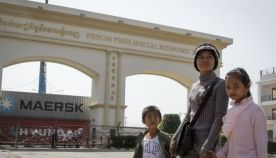 People walk past the entrance of Phnom Penh Special Economic Zone in 2013.