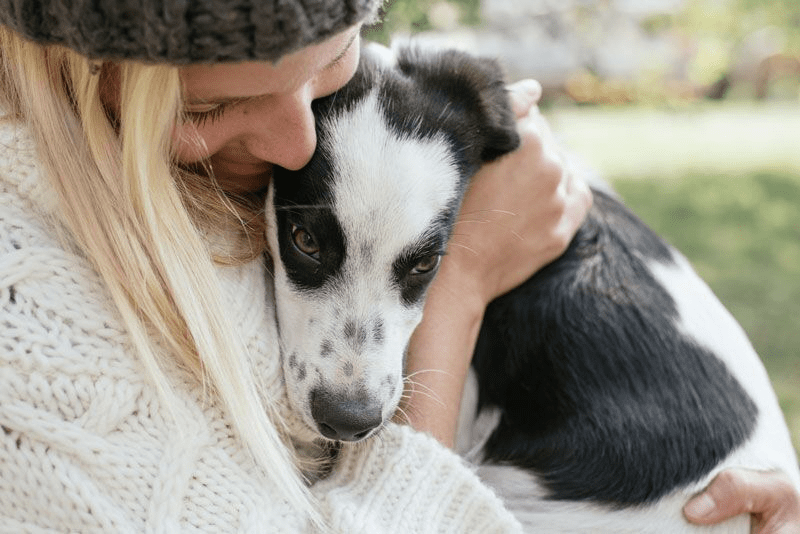 woman hugging a spotted puppy