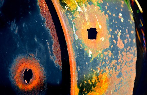 The frame on a rusting oil drum reveals a creature's happy face.