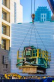 Graphic, crane lifts heavy metal construction module in city